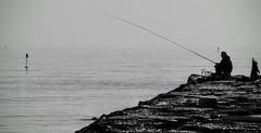Waiting patiently (Agath (Sonia)) Tags: sea blackandwhite cliff backlight fisherman nikon riviera mare riflessi relfections ravenna pescatore romagna nikonnikkor70300 nikond3100
