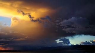 Mount Kailash dwarfed by sunset colored clouds, overlooking Lake Manasarovar, Tibet