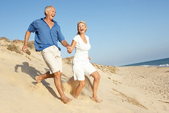 Senior Couple Enjoying Beach Holiday Running D...