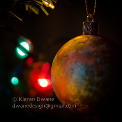 Golden Bauble (Kieran Dwane Photography) Tags: life christmas new xmas winter light red party white holiday abstract black blur color home yellow closeup glitter night ball dark festive season stars fun gold golden still saturated shiny colorful warm december glow dof bright bokeh vibrant decorative background object space traditional year seasonal joy decoration creative sparkle chain celebration ornament card round merry tradition elegant decor kieran bauble celebrate decorate glittery greeting shimmer patterned dwane