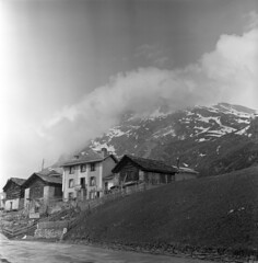 054559 03 (nick dewolf photo archive / s. lundeen, archivist) Tags: road street houses homes blackandwhite bw mountain mountains alps 6x6 tlr film clouds buildings mediumformat switzerland blackwhite europe swiss nick may peak alpine 1950s peaks 1959 snowcovered picketfence dewolf triptoeurope coveredinsnow nickdewolf photographbynickdewolf