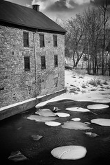 Grist Mill (lynn.h.armstrong) Tags: camera trees windows roof winter chimney sky bw white snow ontario canada black building art mill ice water monochrome stone clouds silver river lens geotagged photography photo interesting mac aperture nikon rocks long flickr afternoon zoom south hill wb images lynn h mortar getty pro nik nikkor armstrong raisin stormont vr licence afs request dx grist sault attribution ingleside 2011 ifed 18200mm f3556 martintown noderivs vrii efex d7000 lynnharmstrong