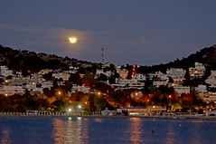Moon eclipse over the town (n.pantazis) Tags: sea sky moon night clouds reflections lights eclipse nightshot streetlamps halo pylon greece moonrise antenna partialeclipse vouliagmeni tamronaf70300mmf456dildmacro