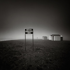 Bathing Dangerous Here (Andy Brown (mrbuk1)) Tags: mist seascape blur beach sign fog sepia danger writing warning dark square person mono coast blackwhite sand solitude mood alone grain atmosphere eerie pebbles creepy devon shore advice remote ghostly desolate barren vignette beachhuts teignmouth lpoty