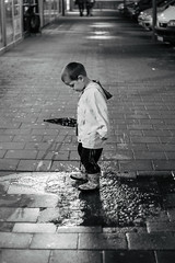 Kids.. (krkojzla) Tags: portrait blackandwhite bw water monochrome smile face look rain childhood kids analog umbrella vintage puddle happy kid child play grain happiness monochromatic retro rainy canon5d angrymom canon50mmf18stm