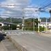 JR「宮野駅」→バス停「宮野駅前」 005 つきあたりの道路に出たら、写真右にある不動産屋さんの前の横断歩道をわたって、右に曲がると、黄色い看板の美容室が見えます。