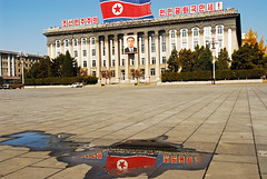 PRK-Pyongyang-0811-284-v1 (anthonyasael) Tags: travel sky people urban reflection building male water horizontal architecture buildings one reflecting asia republic exterior pavement no flag politics authority north places nobody courtyard scene palace korea flags structure east communism korean reflect politicians anthony destination government script patriotism far democratic pyongyang likeness dprk nonwestern asael of