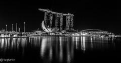 Marina Bay Sand (explored) (Lucy Burtin) Tags: bridge blackandwhite water monochrome blackbackground skyline architecture night