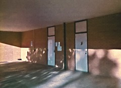Breezeway (rileymillion) Tags: school shadow building architecture bench concrete doors 35mmfilm disposablecamera analogphotography lateafternoon breezeway adamselementary colorfilm color35mm