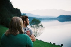 Katy and Chris, Hallstttersee (Tom Spearing) Tags: travel trees sunset summer portrait lake mountains reflection film analog 35mm landscape photography 50mm austria haze superia roadtrip fujifilm analogue 18 zuiko olympusom2n hallstttersee photographersontumblr tomspearing