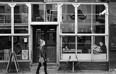 Walking Past (preynolds) Tags: windows blackandwhite london mono restaurant cafe streetphotography shoreditch readingthenewspaper 600d walkingpast tamron1750mm