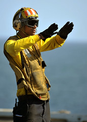 A Sailor directs aircraft during flight operations. (Official U.S. Navy Imagery) Tags: aircraftcarrier usnavy atsea cvn72 ussabrahamlincoln nimitzclass ussabrahamlincolncvn72 brianmorales usnorthcom wwwfacebookcomusnavy