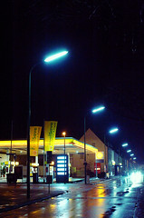 Gas Station (andersdenkend) Tags: street blue black wet car rain yellow night reflections dark streetlights availablelight shell headlights gasstation tinted afterdark tankstelle moist artificiallight nikkor50mmf12 nikond700