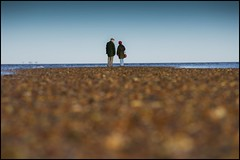 Strangers on the Shore (adrians_art) Tags: people beach coast couple stones shingles perspectives bluesky pebbles shore groundlevel whitstable seawater thestreet