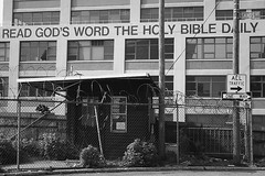 God's Word_3358 (Punk Dolphin) Tags: street newyorkcity windows blackandwhite bw signs building wall brooklyn fence bricks barbedwire oneway curve shrubbery guardhouse alltraffic sandsstreet