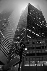 into thick air | 53rd + lex | nyc (elmofoto) Tags: nyc bw mist newyork bus monochrome sign fog night skyscraper evening vanishingpoin