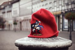 Batman on a mission to save a smalltown (ms holmes) Tags: red hat comic post random super depthoffield hero batman marketplace held mtze marktplatz rote shallowdof pfahl canoneos1000d
