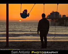A Swingin Sunset at the Oceanside Pier (Sam Antonio Photography) Tags: california christmas sunset water silhouette yellow pier sand sandiego father daughter swing lakemichigan pacificocean oceanside santaclaus merry merrychristmas beachsunset warmlight oceansidepier northcounty candidphotography peoplephotography christmasspirit pacificsunset sandiegosunset sandiegobeach oceansidebeach samantonio samantoniophotographycom