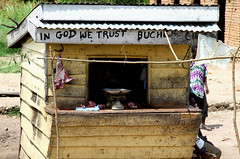 In God We Trust Bucher (cowyeow) Tags: poverty africa travel food sign yellow shop rural town scary funny village god market african traditional faith religion humor shed belief meat christian wrong butcher faded crap forgotten badsign vendor shack christianity uganda wtf decrepit filthy misspelled useless funnysign butchery misspell fail funnyenglish funnyafrica kiburara