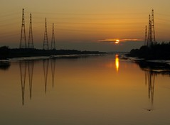 Slow Sunset at Preston (Tony Worrall Foto) Tags: uk sunset england sun color reflection nature wet water beautiful beauty lines electric river gold golden photo nice glow colours power natural northwest image great north stock scenic sunny lancashire estuary excellent preston glowing serene colourful sunlit pylons banks shimmer lancs ribble prestondocks prestonian 2011tonyworrall