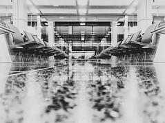 reflect. {explored} (theperplexingparadox) Tags: travel blackandwhite bw reflection monochrome architecture canon switzerland airport pov swiss zurich explore symmetrical zrich emptyseats floorshot emptychairs explored canons90
