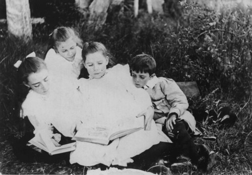 Group of children sitting on the grass reading...