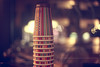 coffee caps pyramid... on Bergerstrasse. (acmi) Tags: window colors warm tea bokeh caps cap nightphoto coffe piramide hotdrinks chailatte warmplace coffeteria coloredcaps pepercaps