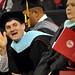 Graduate student happily waves to family sitting in the RBC Center crowd.