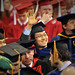 Graduate student waves to family and friends.