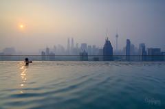 Kuala Lumpur Hazy Morning View From Infinity Pool (Syafiqjay) Tags: blue sky sun man tower water pool haze cityscape infinity ngc wave malaysia kuala splash kl klcc lumpur regalia skyscrapper sunise syafiqjay