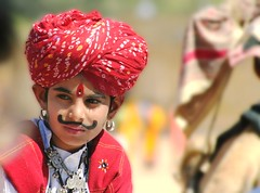 Prince Ali.. (areyarey) Tags: travel boy red portrait india face festival eyes eyelashes desert little expression decoration culture prince moustache earrings festivity turban festivities jaisalmer rajasthan bindi tash areyarey