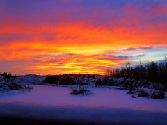Burning sunset skies over a cold, winter wonderland (peggyhr) Tags: blue trees friends sunset sky orange white snow canada black reflection yellow clouds island silhouettes hills alberta mauve bluehour frozenlake snowylandscape peggyhr snowcoveredlake flickrbronzeaward bestsun heartawards bluebirdestates artofimages mygearandme ringexcellence blinkagainforinterestingimages bestofblinkwinners redgroupno1 yellowgroupno2 soloastroreisunthestarking p1110942ap