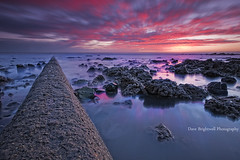 The Pipe (Dave Brightwell) Tags: pink red beach clouds sunrise reflections rocks sony pipe sigma sewage easington
