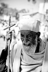 portrait of a religious pilgrimage with a stickin the shape of cross celebrates the festival Hosanna (Palm Sunday) in Axum, tigray (anthony pappone photography) Tags: africa travel portrait bw canon blackwhite cross afrika priest ethiopia orthodox ritratto viaggio coptic pilgrim axum afrique etiopia   tigray tigrinya   hosaina tigrini  kililoch