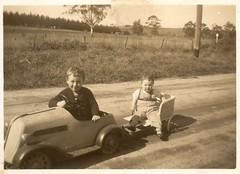 Two young boys in a pedal car and trailer (undated) (pellethepoet) Tags: boys kids rural children brothers snapshot australia siblings photograph countryroad pedalcar