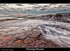 Flowing Dreams (John_Armytage) Tags: seascape clouds sunrise landscape movement rocks waves textures newport 5d canon1635l neportbeach canon5dmark1 johnarmytage wwwjohnarmytagephotographycom