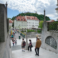 People walking down the Ljubljanica river (Bn) Tags: street old city trip summer people holiday streets men castle history church river walking square geotagged town women energy europe child market small hill capital sightseeing relaxing scenic atmosphere pedestria