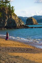 Beach stroller (Ruwan W) Tags: sea newzealand sky cliff mountain tree girl sunglasses walking sand nw nz stroll strolling