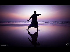 The only person you should ever compete with is yourself.  You can't hope for a fairer match. (Yug_and_her) Tags: travel sea india man reflection beach water silhouette concentration twilight focus waves dusk goa solo practice taichi arambol