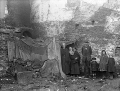 February 2, 1924 (National Library of Ireland on The Commons) Tags: family tent canvas burlap sacks poverty homeless grandmother mother father children shawl boots caps smiling derelict rubbish mud alexanderstreet waterford ireland munster ahpoole arthurhenripoole poolecollection glassnegative nationallibraryofireland 99