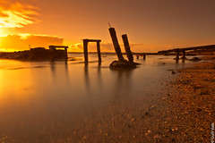 Wood posts in sea - Iceland. (Gulli Vals) Tags: ocean city trip blue winter friends sunset red sea orange cliff sun sunlight white seascape blac