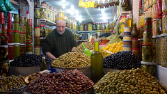 Marrakech - Place Jamma El Fna - Souk Aux Olives (aminefassi) Tags: africa plaza travel portrait people copyright food man shop lumix downtown noir magasin commerce piment place muslim olive violet culture vert arabic panasonic morocco boutique maroc oil condiment marrakech maghreb souk medina marrakesh citrus tradition oliva citron nourriture marokko 43 2012 huile afrique  conserve fna mediterrane  mft zeytin maroko  jemmaelfna marrakchi  marueccos  commercant   huiledolive gf3       microfourthirds  14mmf25    aminefassi
