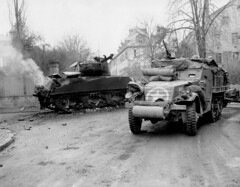 An M3A1 half-track passes close to a knocked out Sherman M4A3 tank. The tank commander, who is visible just outside the turret, was killed in action during the German attack that destoyed his tank in the town of Barr in France's Alsace region. November 29, 1944