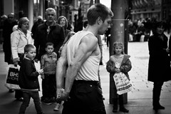 Filled with Awe and Wonder (Leanne Boulton) Tags: life lighting street city light shadow portrait people urban blackandwhite bw white man motion black detail male texture monochrome face muscles childhood modern canon shopping children wonder mono scotland living blackwhite movement aperture focus dof looking dynamic faces natural bokeh outdoor expression glasgow candid crowd watching young streetphotography pedestrian scene entertainment human buchanan shade portraiture area streetperformer acrobat entertainer backlit posture amazement busker juggler bandw awe drama performer depth tone facial poise zone flexing candidstreetphotography