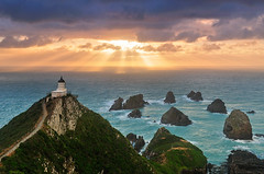 Nugget Point (Mike Isaak) Tags: ocean blue trees newzealand panorama orange lighthouse green nature water yellow clouds sunrise landscape photography coast solar amazing nikon rocks photographer hiking pano naturallight panoramic hike otago coastline filters epic hdr fineartphotography waterscape nuggetpoint solarpowered godlight travelphotography gnd nuggetpointlighthouse d300s mikeisaak wwwmikeisaakcom