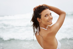 Attractive young woman in bikini smiling at you on a beach (Certified Plastic Surgeons) Tags: ocean life sea summer vacation portrait sky people woman white hot sexy beach wet water girl beautiful beauty smile smiling modern lady female standing fun happy person freedom model women surf hand looking adult natural bright body background space young happiness fresh human bikini attractive leisure copyspace seductive copy femininity