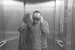 it's a kiss in a lift (Thomas Hole) Tags: city bw man london girl hotel lowlight kiss fuji lift coventgarden f2 boyandgirl bigsmoke movingup x100 thomashole fujix100