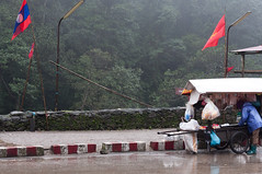 crossing a border to Laos (hafual) Tags: wood morning light woman mountain lamp berg rain fog forest asian lampe licht town stand asia asien nebel cross flag hill border vietnam stadt frau laos sell wald morgen flagge lao regen verkaufen reise grenze worldtour weltreise berqueren asiatin triparoundtheworld viangchan
