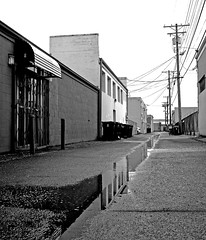 Empty alleyway () Tags: street old city bw blur reflection wet water pool architecture buildings grit puddle concrete photo washington interesting alley view state pacific northwest image district picture gritty historic neighborhood photograph alleyway local tacoma depth rainwater southtacomaway gritcity fieldurban
