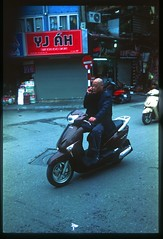In touch on the move (jeremyhughes) Tags: vietnam hanoi hni scooter mobilephone cellphone onthemove communication man rider street urban city phonecall phone phoning conversation mobile mobility motorcycle nikon f90x nikonf90x slidefilm transparency film fuji fujifilm scan scanned